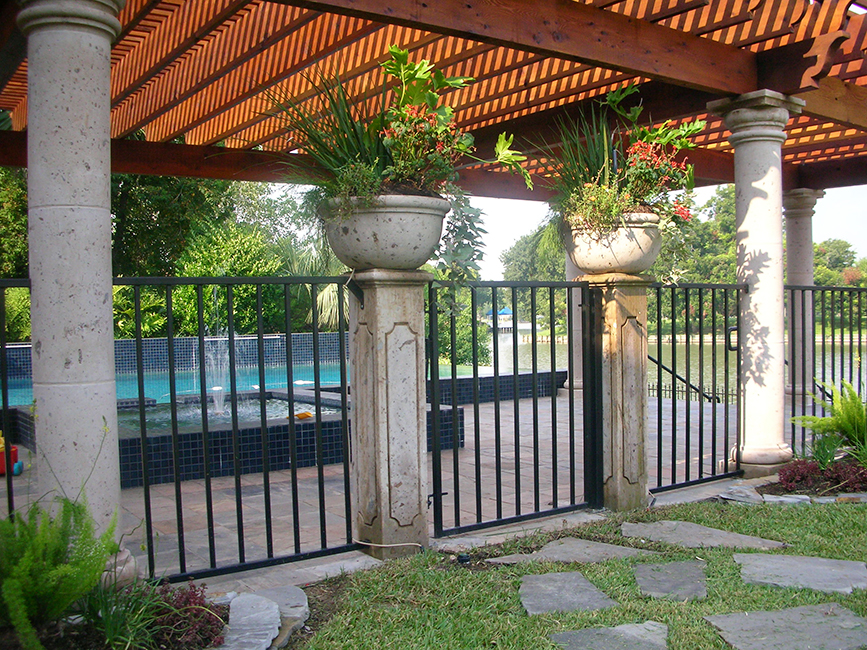 Cantera Stoneworks pedestals web banner with image of backyard pool, cantera stone arbor, pedestals, & urn planters.